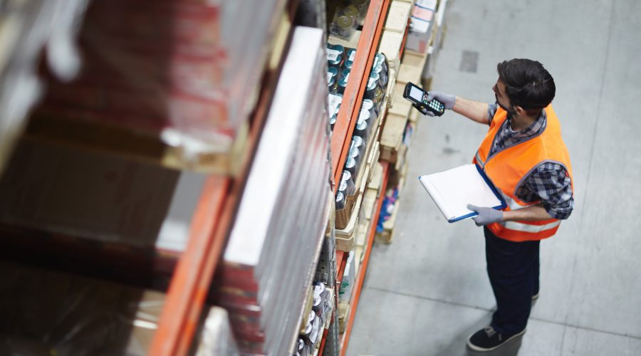 Warehouse manager checking inventory by scanning bar-codes